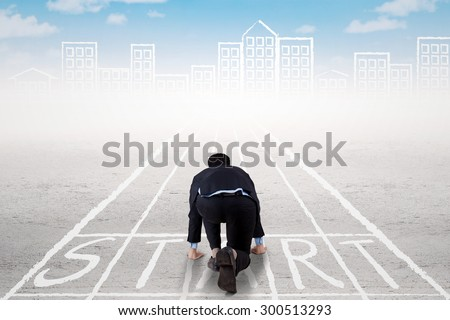 Rear view of businessman with ready position to compete on the start line - stock photo
