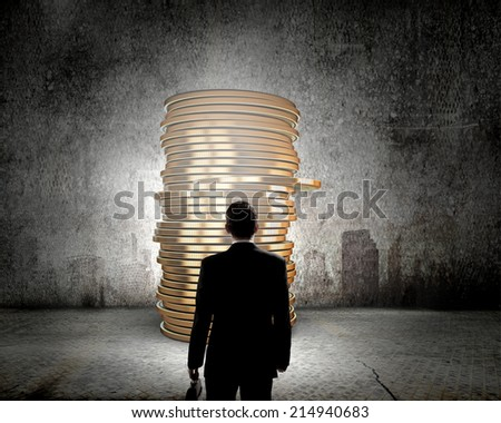 Rear view of businessman with suitcase looking at stack of coins - stock photo