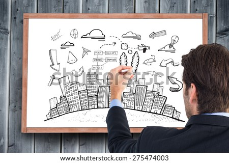 Rear view of businessman writing with a white chalk against blackboard with copy space on wooden board - stock photo