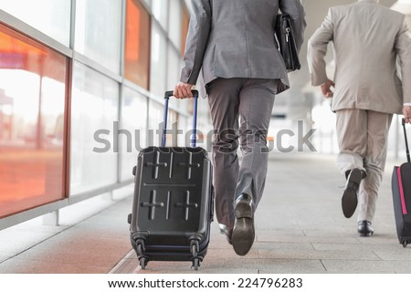 Rear view of businessmen with luggage running on railroad platform - stock photo