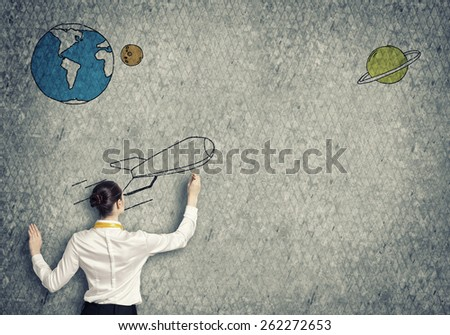 Rear view of businesswoman drawing rocket on wall - stock photo