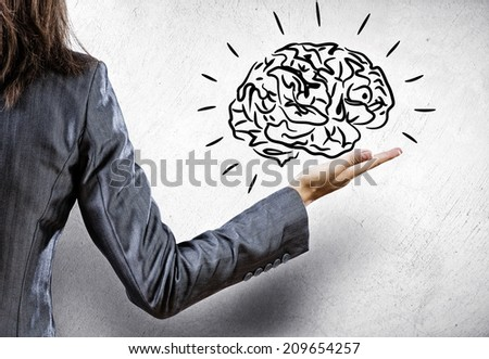 Rear view of businesswoman holding human brain in palm - stock photo