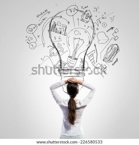 Rear view of businesswoman looking thoughtfully at business sketches - stock photo