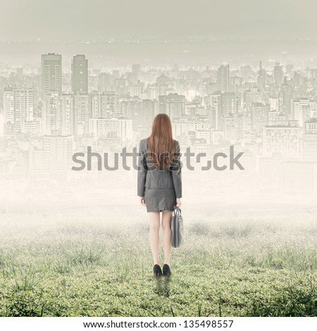 Rear view of businesswoman stand on grassland in city. - stock photo