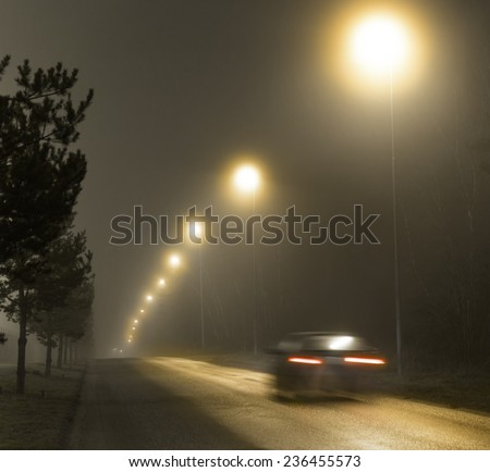 Rear view of car in blurred motion on country road on foggy night - stock photo
