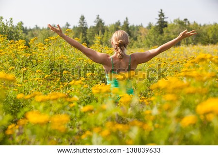 rear view of Caucasian blonde middle-aged woman practicing yoga arms stretched in the middle of a meadow of yellow ragweed flowers.  Blue Hill, Maine, Summer - stock photo