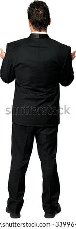 Rear view of Caucasian man with short black hair in a tuxedo holding invisible object - Isolated - stock photo