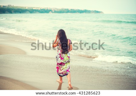 Rear view of child walking along the seacoast. Girl in a colorful dress walking on the beach - stock photo