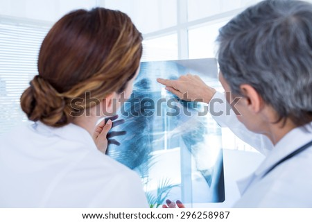 Rear view of concentrated medical colleagues examining x-ray together in the hospital - stock photo