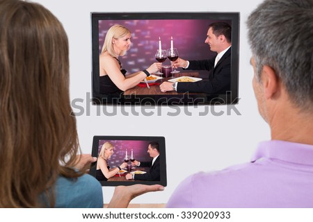 Rear View Of Couple Connecting Television Channel Through Wifi On Digital Tablet - stock photo