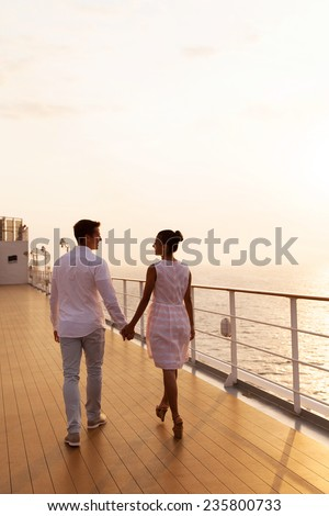 rear view of couple holding hands walking on cruise ship - stock photo