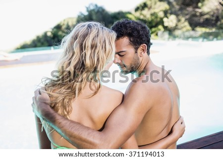 Rear view of couple sitting by the pool nose to nose - stock photo