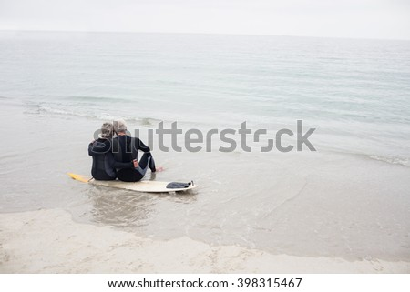 Rear view of couple sitting on surfboard at beach - stock photo
