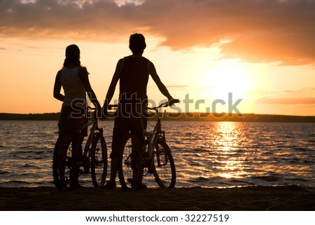 Rear view of couple standing on seashore with their bicycles and enjoying sunset - stock photo