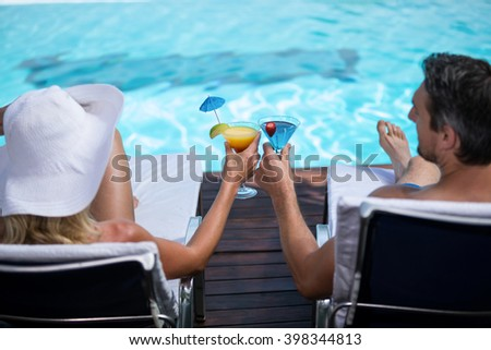 Rear view of couple toasting martini glass while relaxing on sun lounger near pool - stock photo