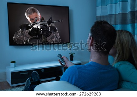 Rear View Of Couple Watching Film In Living Room - stock photo