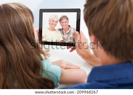 Rear view of daughter with father video chatting on digital tablet at home - stock photo