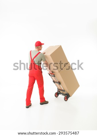 rear view of delivery man holding push cart loaded with cardboard boxes, on white background. copy space available - stock photo
