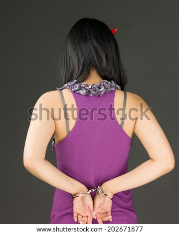 Rear view of devil side of a young Asian woman with handcuffs - stock photo