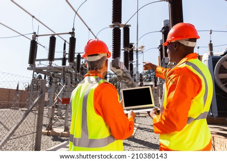 rear view of electricians with laptop pointing in substation - stock photo
