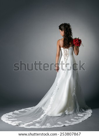 Rear view of elegant bride in dress with plume - stock photo