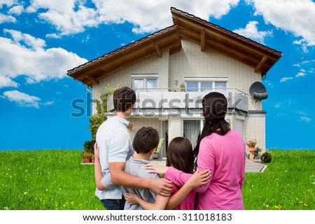 Rear view of family looking at new house on grassy field against sky - stock photo