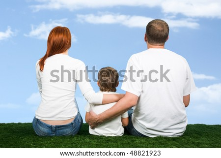 Rear view of family sitting together and looking at sky - stock photo