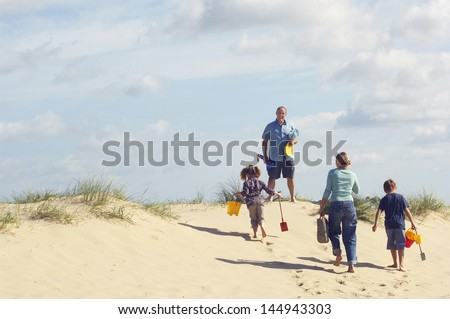 Rear view of family walking up sand dune on beach against the sky - stock photo