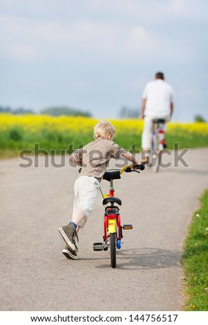 rear view of father and son riding bikes - stock photo