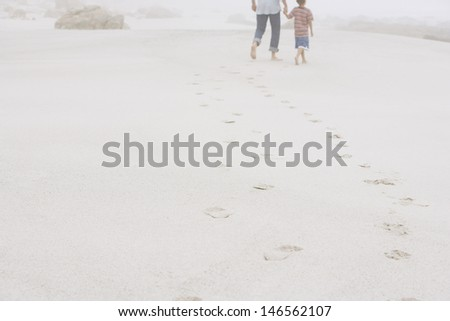 Rear view of father and son walking leaving behind footprints on sand at beach - stock photo