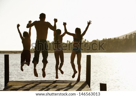 Rear view of father with children holding hands while jumping off a jetty - stock photo