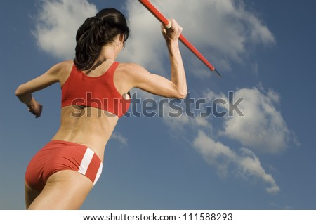 Rear view of female athlete in sportswear throwing javelin - stock photo