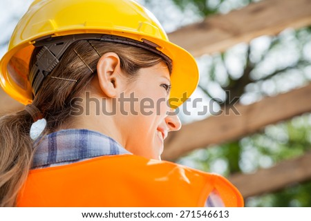 Rear view of female construction worker looking away at site - stock photo