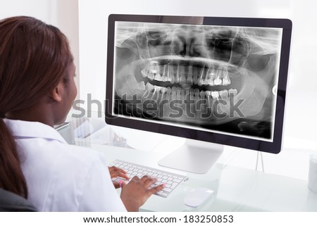 Rear view of female dentist examining jaw Xray on computer in clinic - stock photo