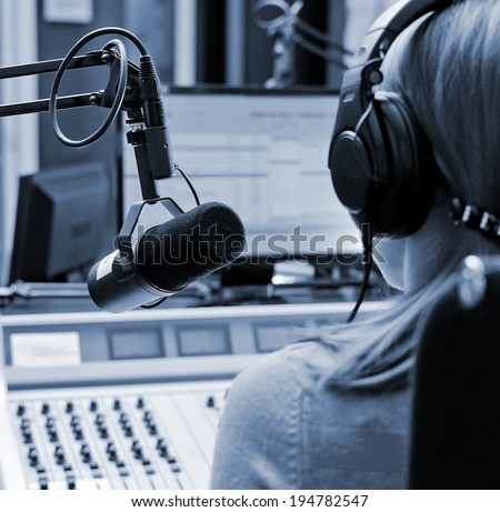 Rear view of female dj working in front of a microphone on the radio - stock photo