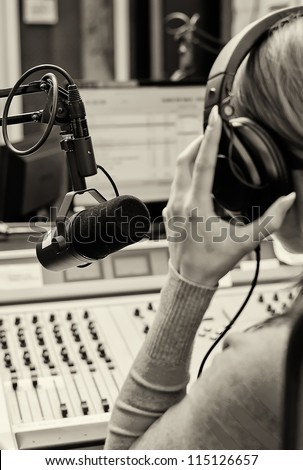 Rear view of female dj working in front of a microphone on the radio. Black and white - stock photo