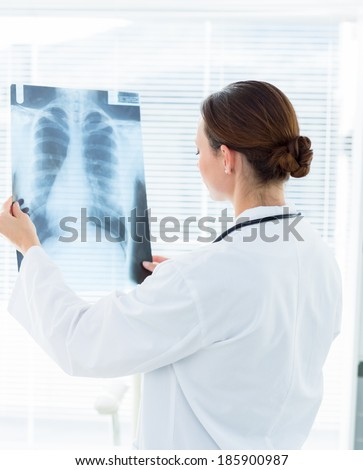 Rear view of female doctor analyzing Xray report in clinic - stock photo