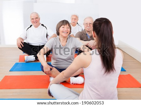 Rear view of female trainer training senior customers on floor in yoga class - stock photo