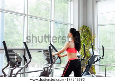 rear view of fit woman sport exercising at the gym on an x-trainer cardio machine, fitness center - stock photo