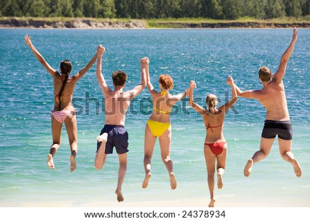 Rear view of friends holding by hands and jumping into water - stock photo