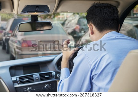 Rear view of furious young man driving a car on the road at the traffic jam - stock photo