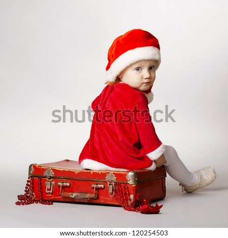 Rear view of girl with Santa cap sitting on suitcase with gifts - stock photo
