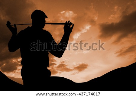 Rear view of golf player holding a golf club against cloudy sky - stock photo