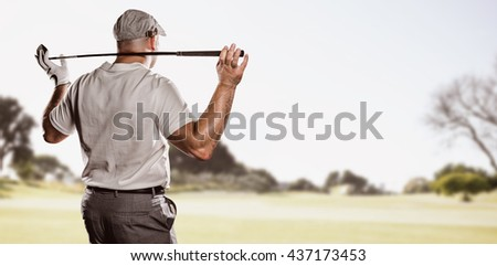 Rear view of golf player holding a golf club against view of a park - stock photo