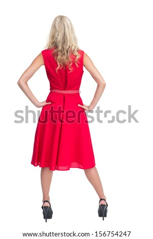 Rear view of gorgeous blonde in red dress posing on white background - stock photo