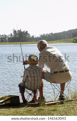 Rear view of grandfather and grandson fishing by lake - stock photo