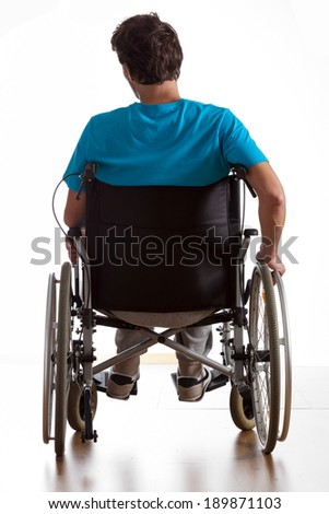 Rear view of handicapped man in wheelchair - stock photo