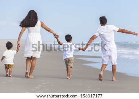 Rear view of happy family of mother, father and two children, boy sons, walking holding hands and having fun in the sand on a sunny beach - stock photo