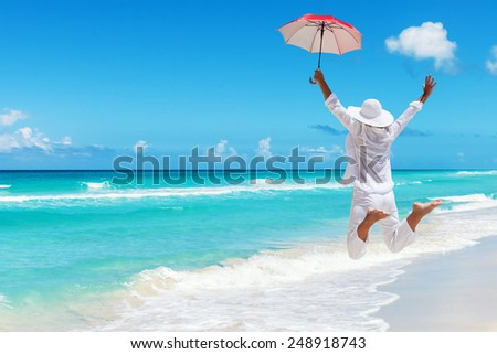 Rear view of happy woman with a umbrella, jumping at Maldives beach.Copy space - stock photo