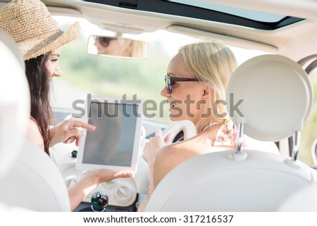 Rear view of happy women using digital tablet in car - stock photo